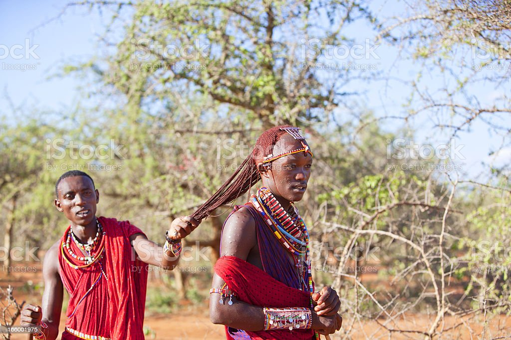Demonstrating the traditional  long red hair of a masai morani. stock photo