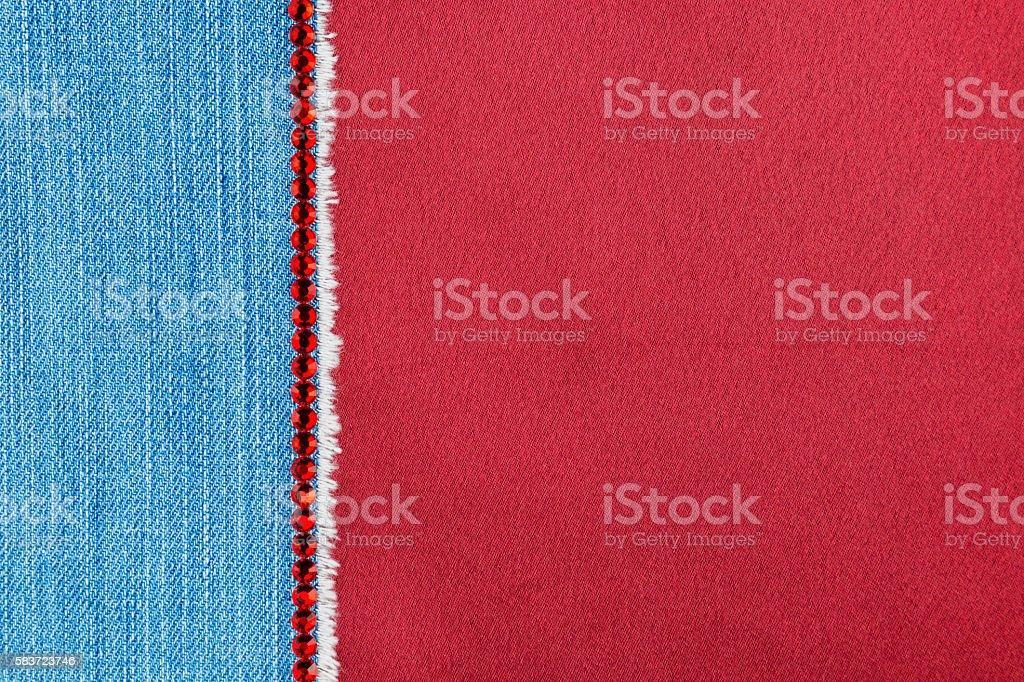 Denim decorated with red rhinestones lying on  satin stock photo