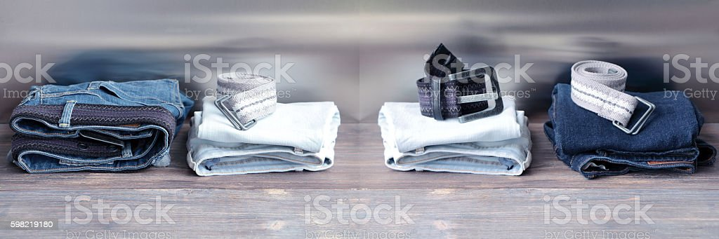 Denim jeans with belts stacked on a wooden board. stock photo