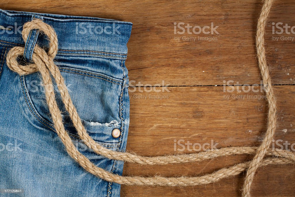 Denim Jeans with rope on a wood background royalty-free stock photo
