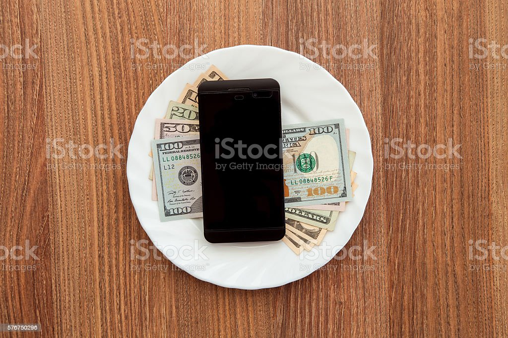 denomination dollars and a black business phone. stock photo