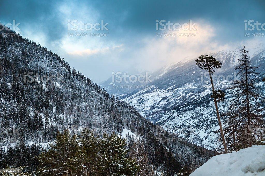 Dense clouds over a wintery mountain valley stock photo