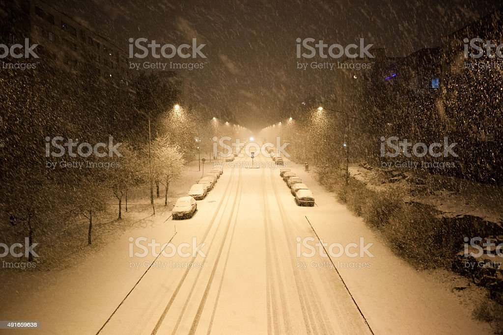 Dense snowfall and empty road at night stock photo