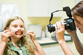 Dental assistant photographs crooked teeth