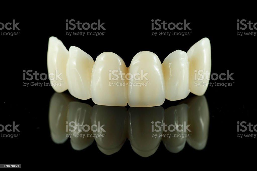 Dental bridge on black background reflecting off surface stock photo