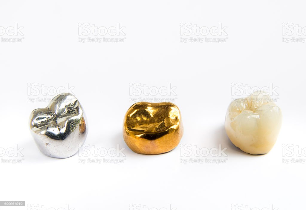 Dental ceramic, gold and metal tooth crowns on white background. stock photo