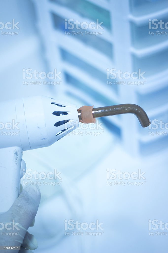 Dental filling gun in dentist hand in clinic office stock photo