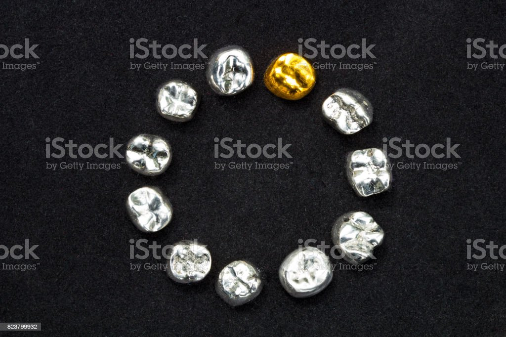 Dental  gold and metal tooth crowns on dark black surface. stock photo