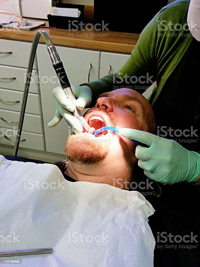 Dental hygienist attending to male patient royalty-free stock photo