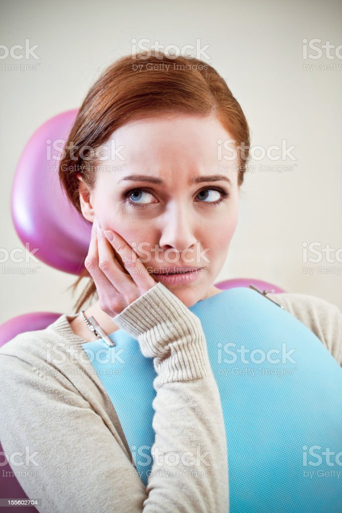 Dental Patient in Exam Chair Holding Jaw royalty-free stock photo