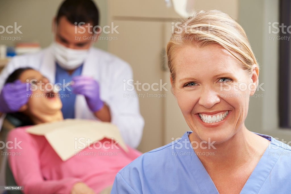 Dental professional smiles as a dentist works on a patient stock photo