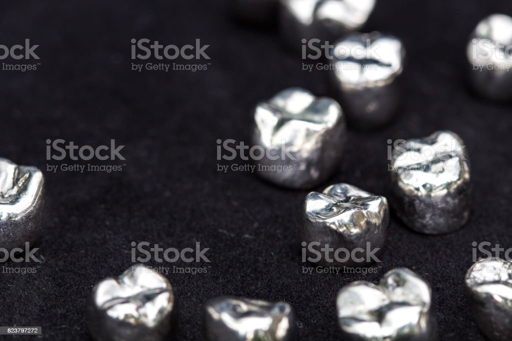Dental silver metal tooth crowns on dark black surface. stock photo