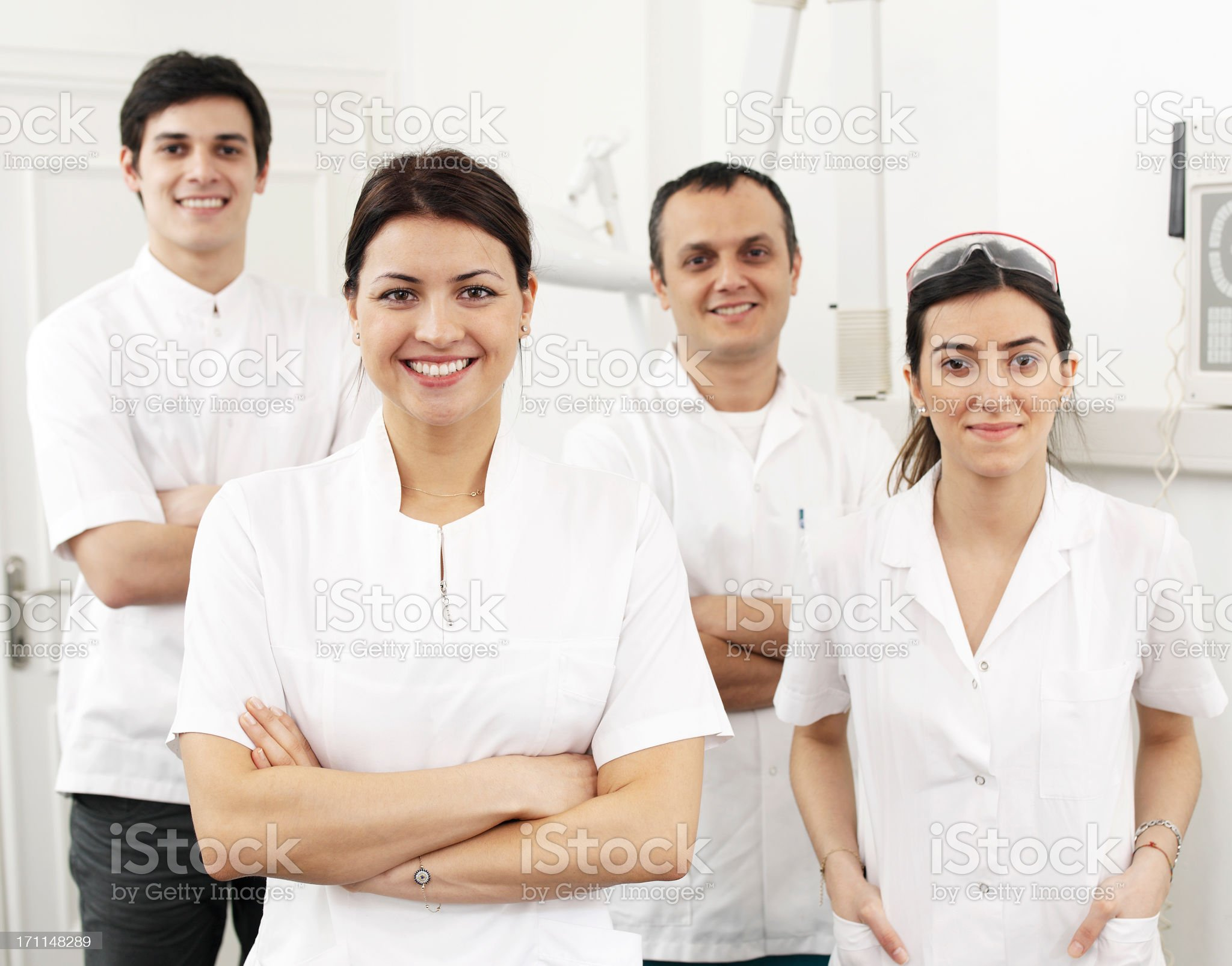 A dental team of two men and two women all in white royalty-free stock photo