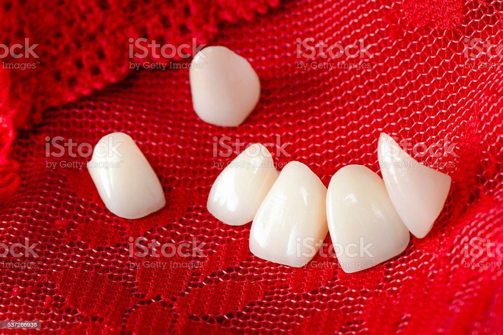 Dental Veneers on Red Lace stock photo