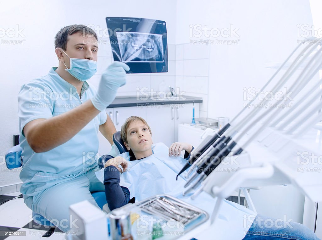 Dentist an his patient looking at x-ray image stock photo