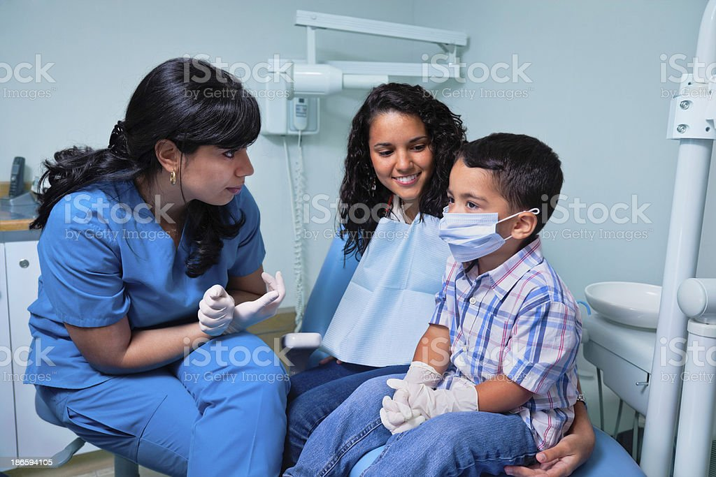 Dentist and mother negotiating with child at dental office royalty-free stock photo