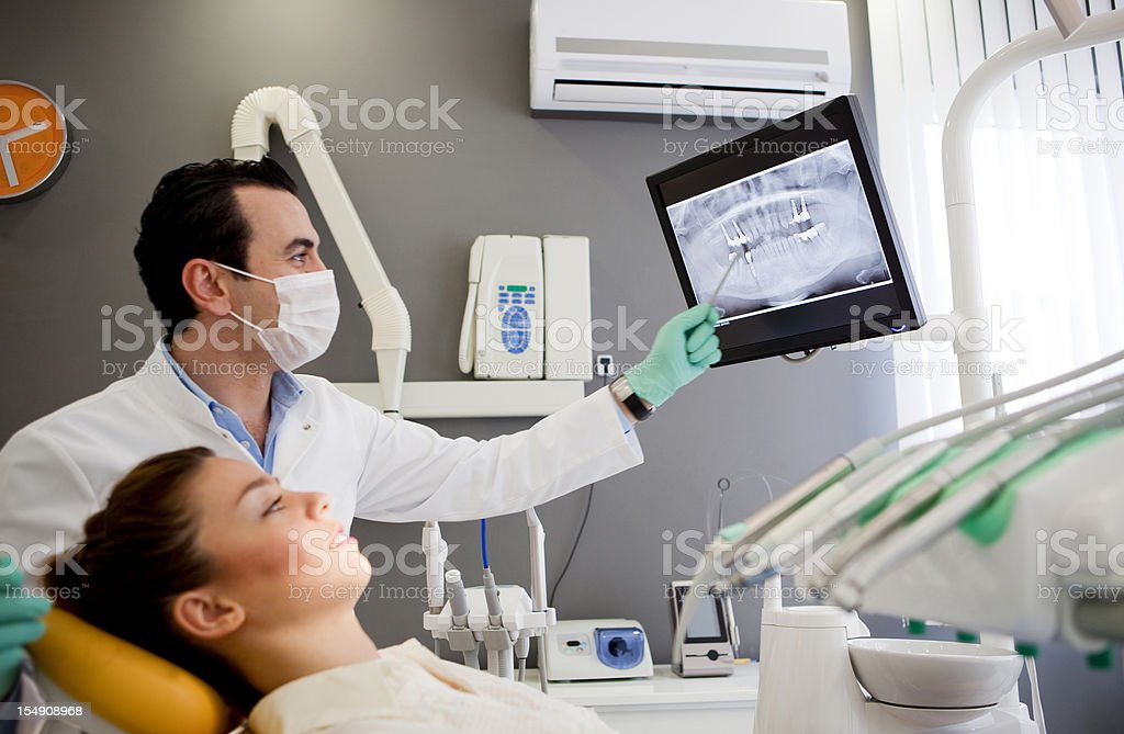 Dentist and patient looking at tooth monitor royalty-free stock photo