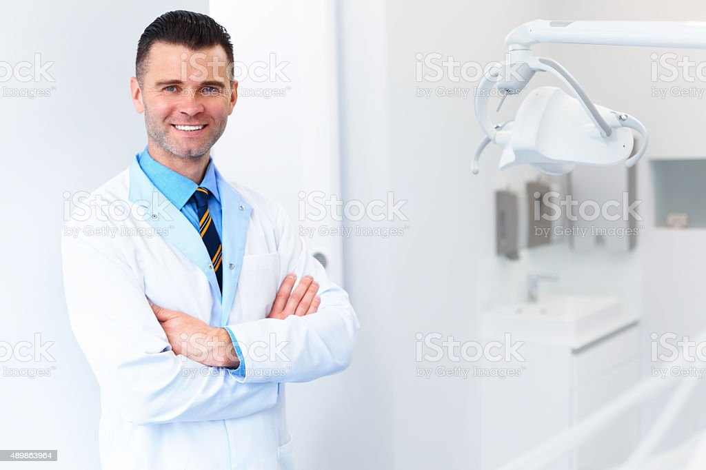 Dentist Doctor Portrait. Young Man at His Workplace. Dental Clin stock photo