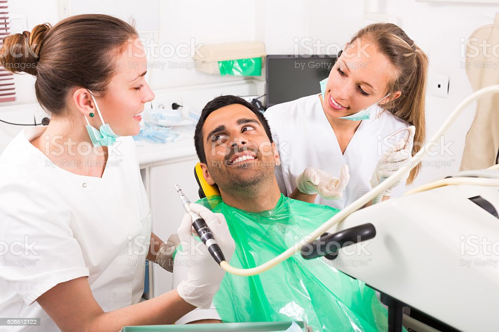 Dentist examines patient at clinic stock photo