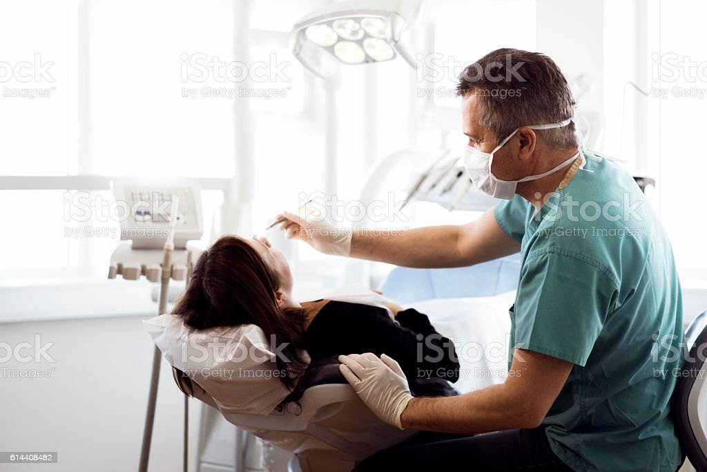 Dentist examining female patient at clinic stock photo