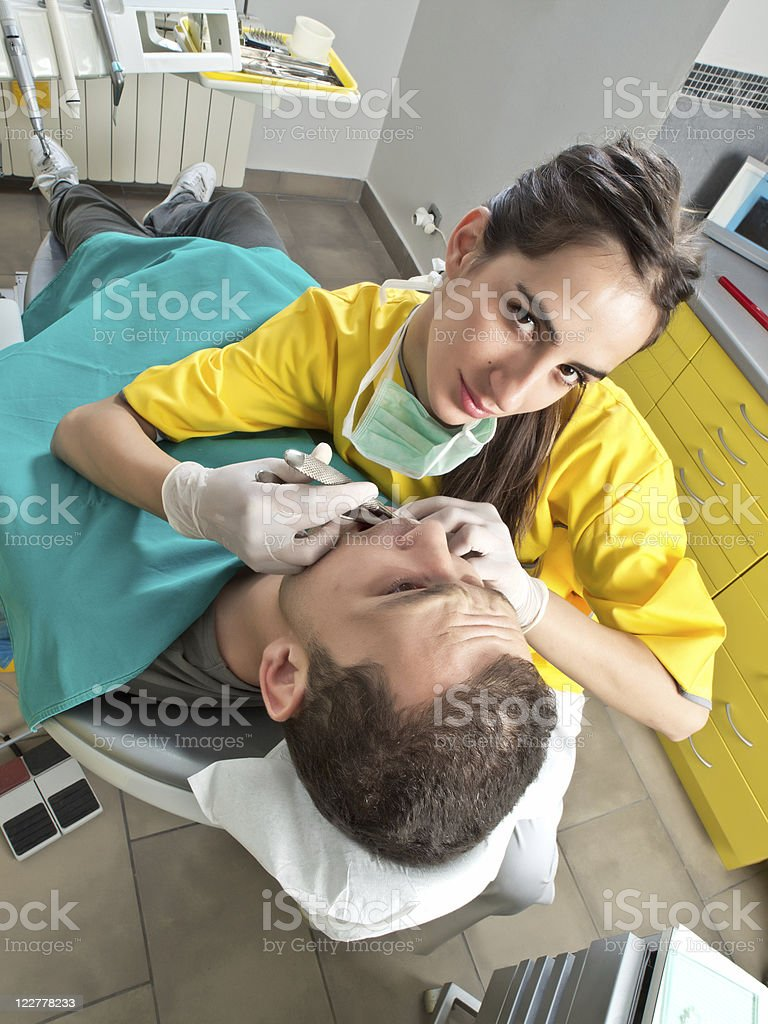 Dentist extracted a tooth to patient royalty-free stock photo