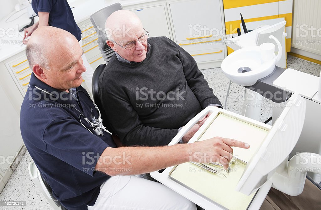 Dentist giving advice to senior patient about dental hygiene royalty-free stock photo