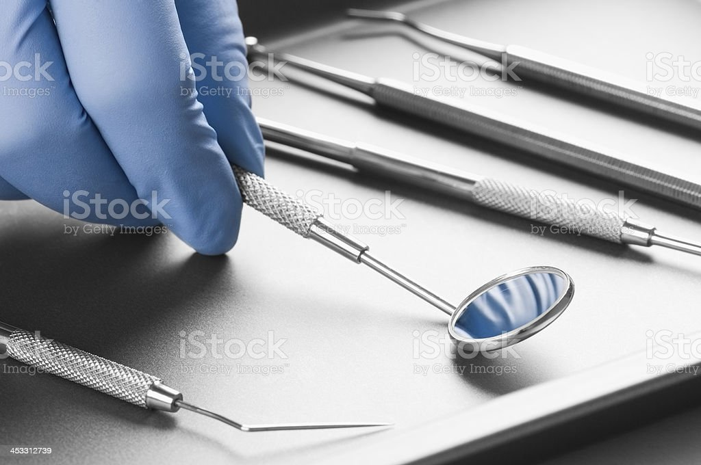 Dentist hand in surgical glove holding dental instrument stock photo