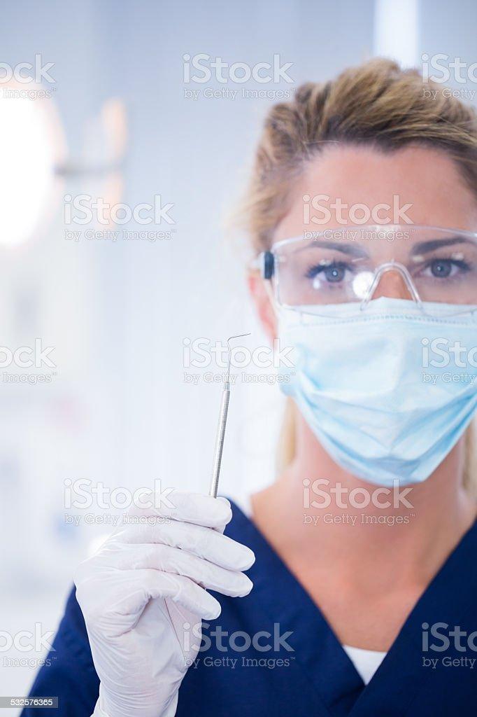 Dentist in mask holding dental explorer stock photo