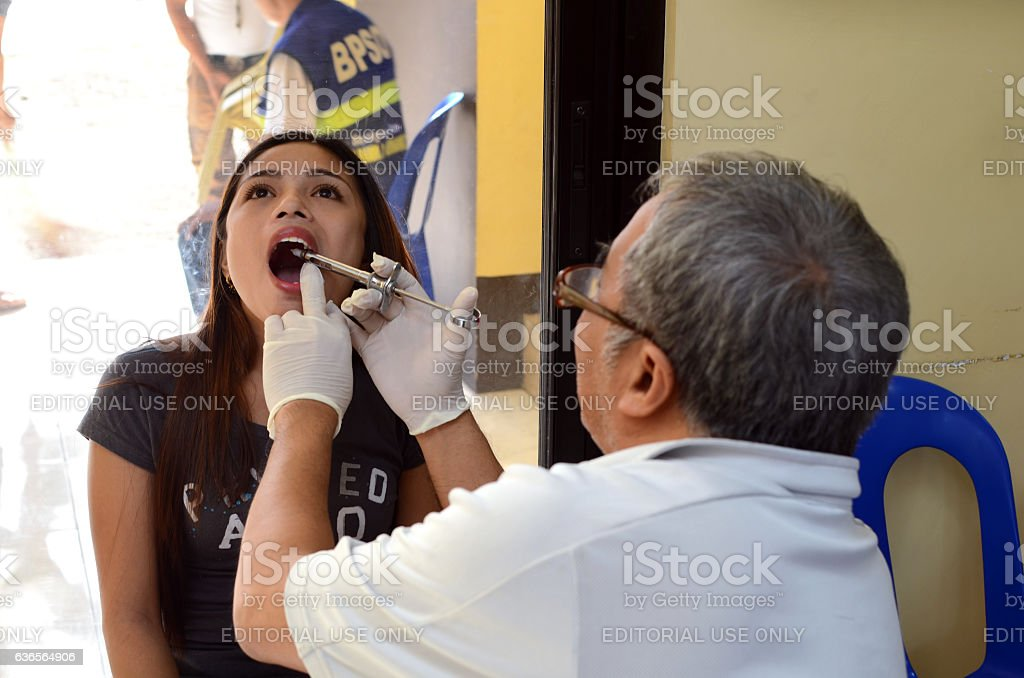 dentist injects anesthesia to the gum of dental patient stock photo
