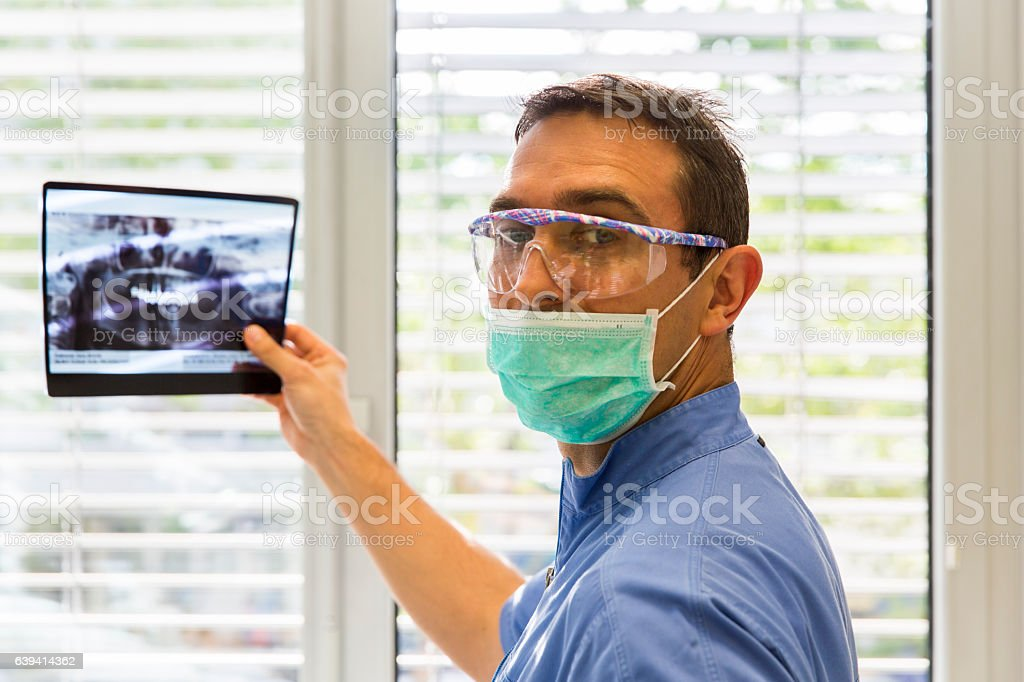 Dentist is examining x-ray of the teeth stock photo