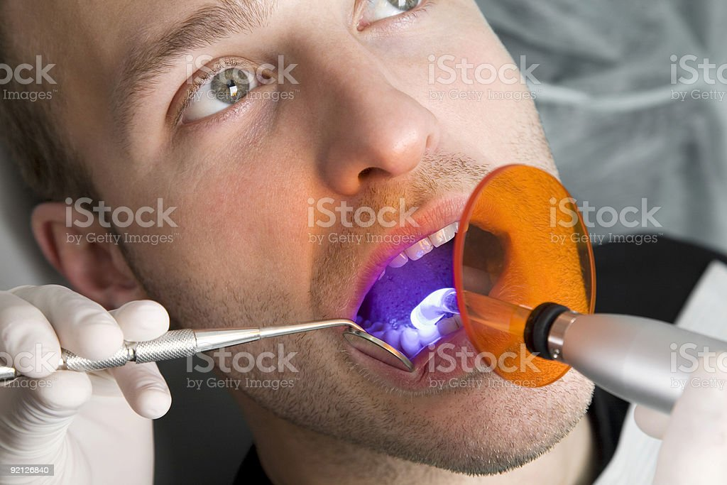 A dentist looking inside a mans mouth royalty-free stock photo