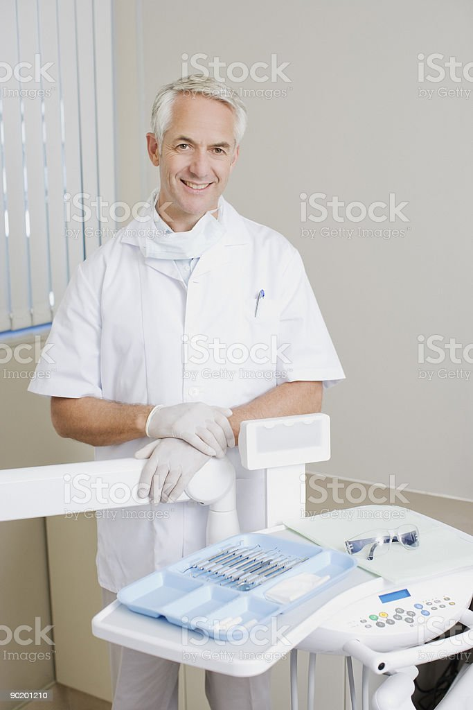 Dentist preparing for examination in examination room royalty-free stock photo