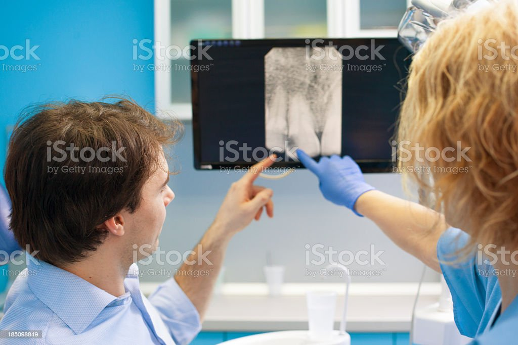 Dentist Professional Explaining  X-Ray Image to Patient royalty-free stock photo