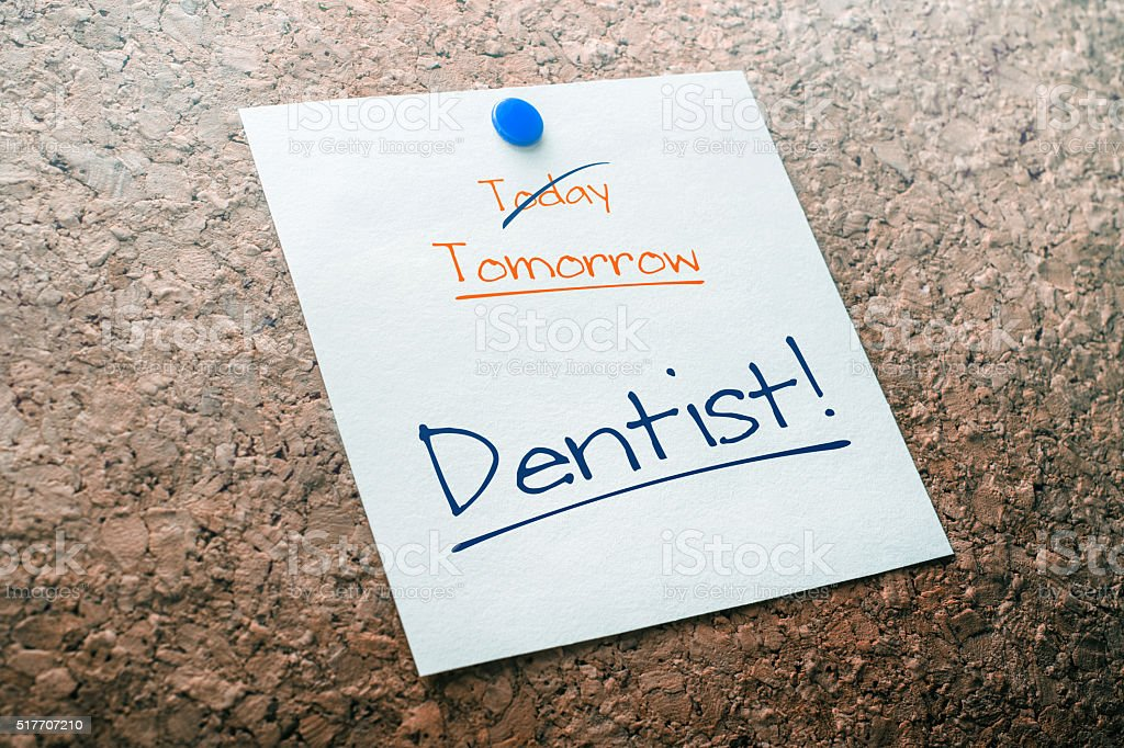 Dentist Reminder For Tomorrow With Crossed Out Today On Cork stock photo