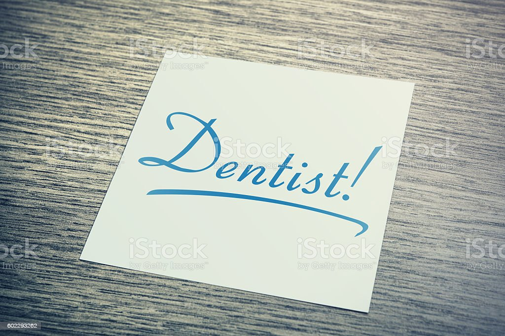 Dentist Reminder On Paper Lying On Wooden Cupboard stock photo