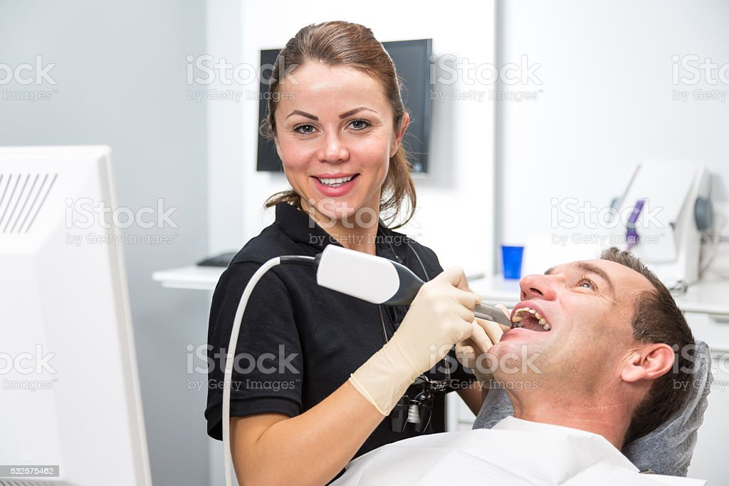 Dentist scanning patient's teeth with CEREC scanner stock photo