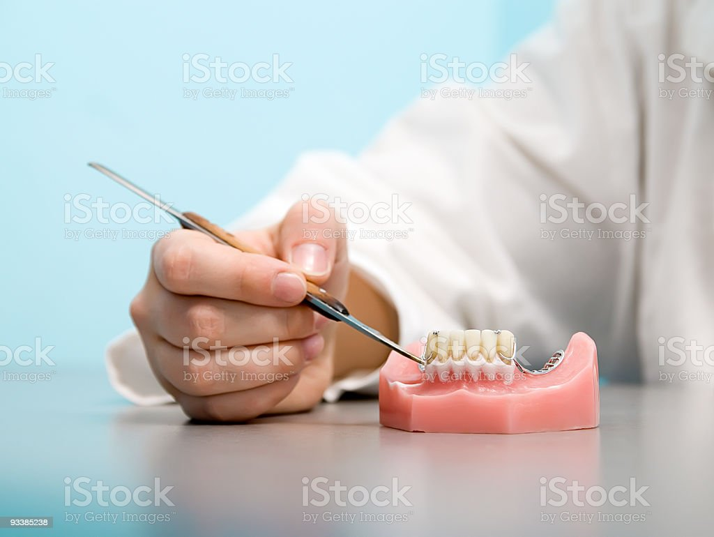 A dentist sculpting a new set of dentures for a patient royalty-free stock photo