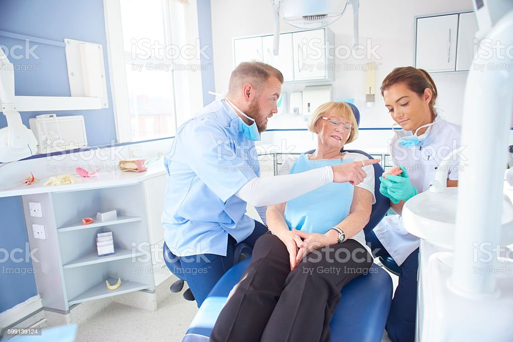 dentist showing senior patient model of dentures stock photo