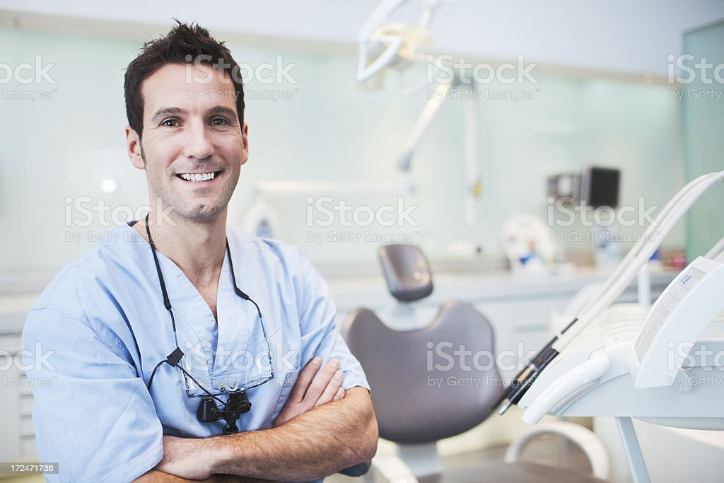 Dentist smiling in exam room stock photo