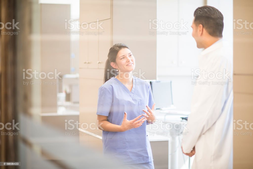 Dentist Speaking with an Assistant stock photo