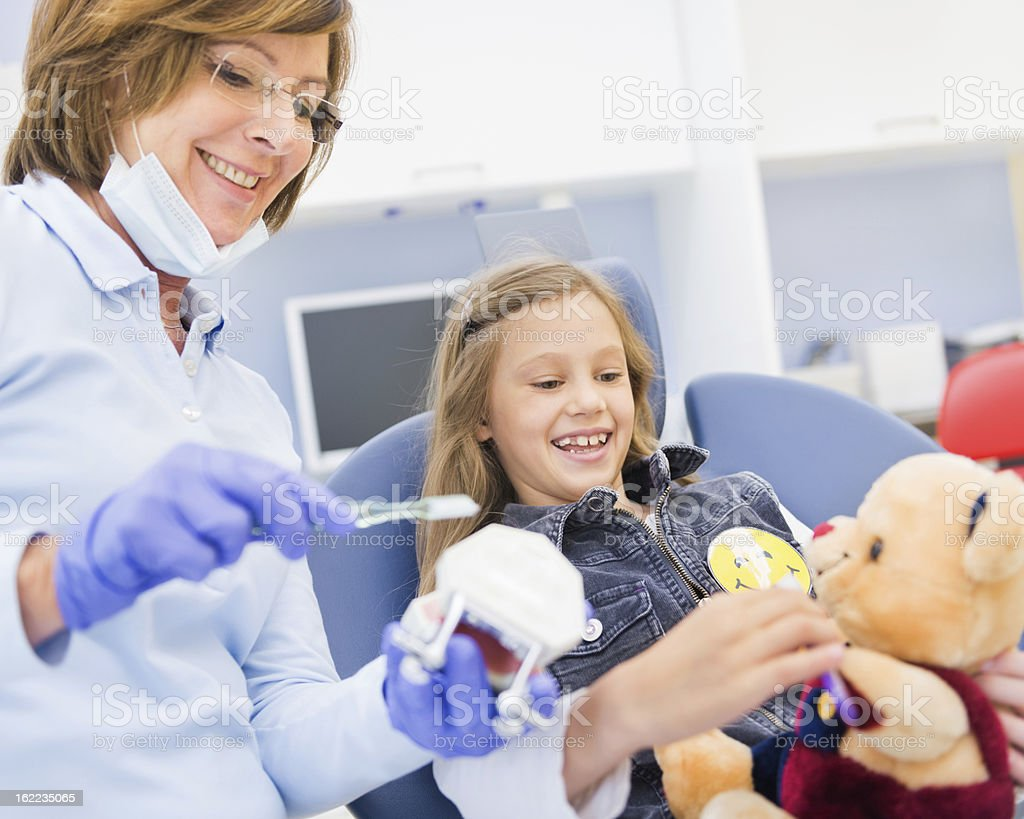 Dentist Teaching Brushing Teeth to a Girl royalty-free stock photo