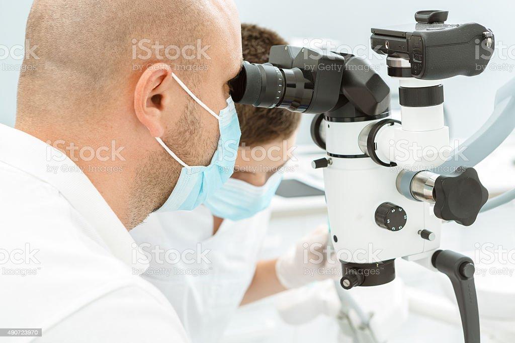 Dentist using dental microscope during inspection stock photo