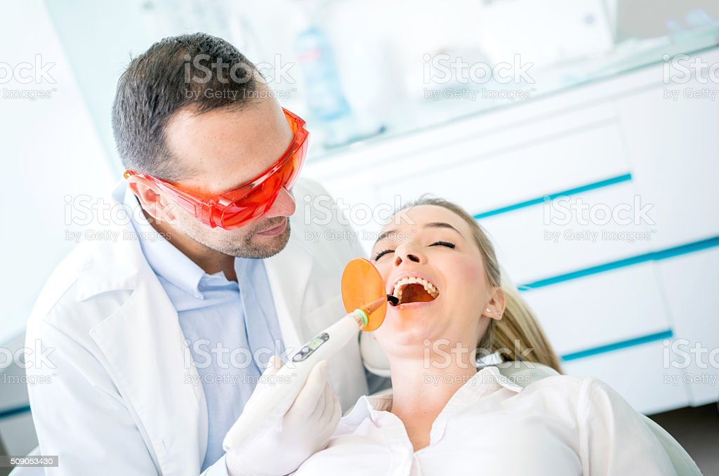 Dentist using laser to fix a cavity stock photo