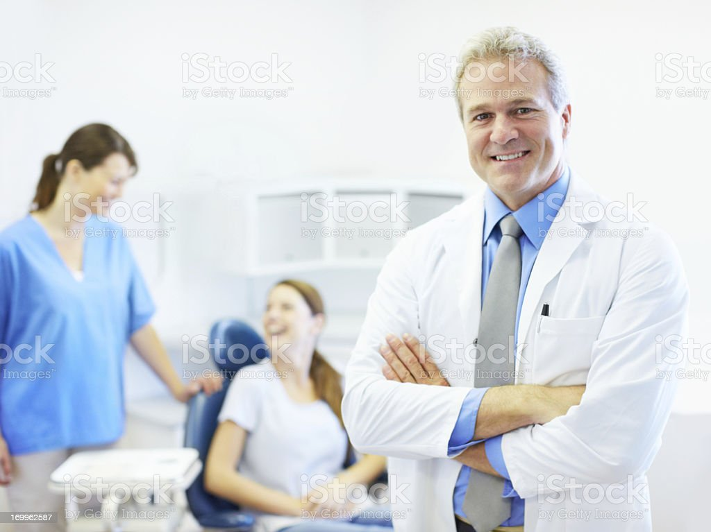 Dentist with patient and staff in background royalty-free stock photo