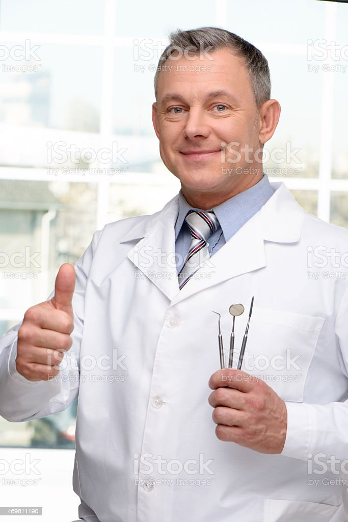 Dentist with tools showing thumb up stock photo