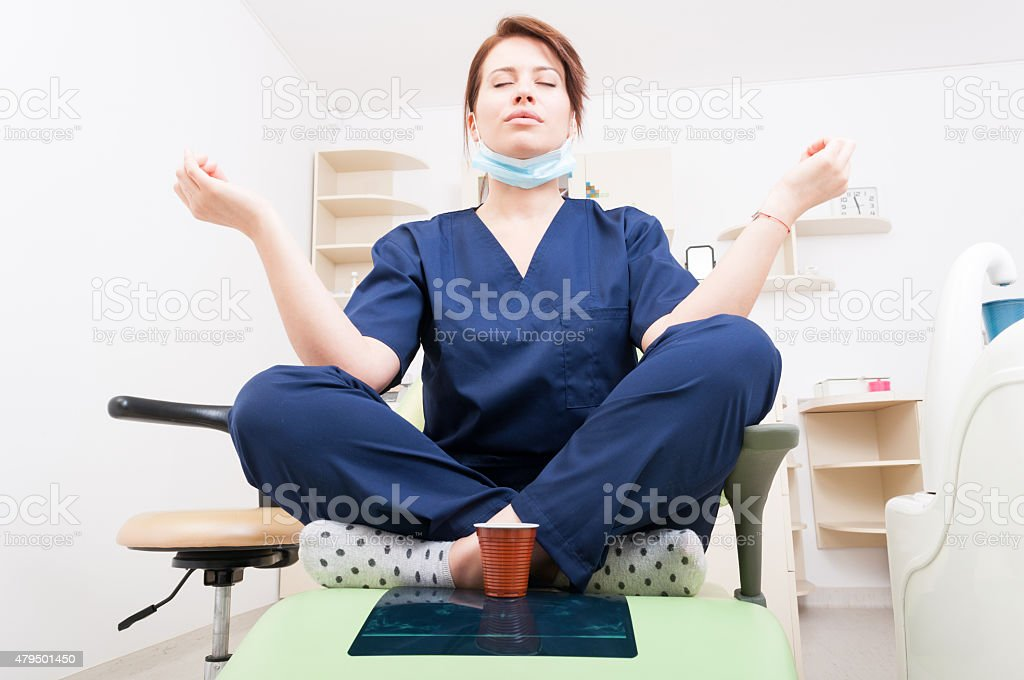 Dentist woman meditating with yoga and lotus position stock photo