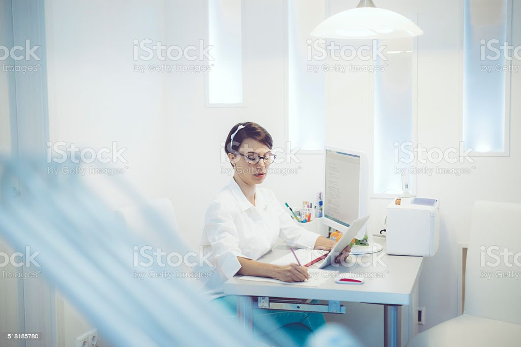Dentist working in her office stock photo