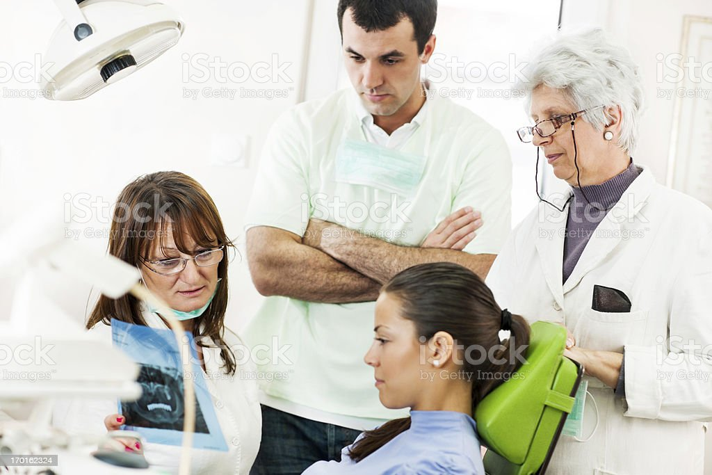 Dentists and patient looking at tooth x-ray royalty-free stock photo