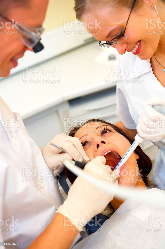 Dentists assisting a female patient royalty-free stock photo