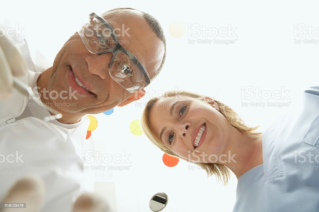 Dentists looking down at patient stock photo